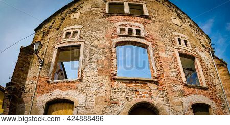 The facade of an old brick destroyed house