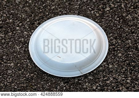 Used And Discarded Flipped And Broken White Disposable Plastic Plate Left On Suburban Family House P