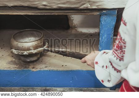 Hostess In Embroidered Clothes Pulled A Pot Of Food Out Of The Oven. Retro Photo Of Ancient Ukrainia