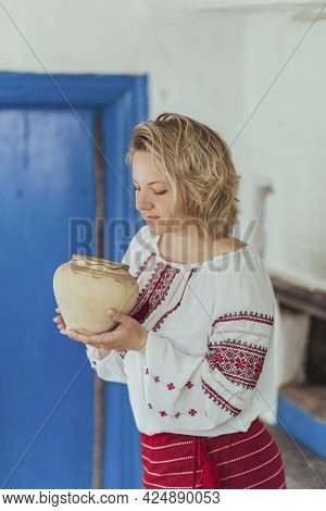 Beautiful Peasant Woman In Embroidered Clothes Inhales The Aroma Of Food In A Clay Pot