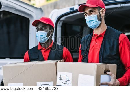 Young Delivery Men Carrying Cardboard Box While Wearing Face Mask To Avoid Corona Virus Spread - Peo