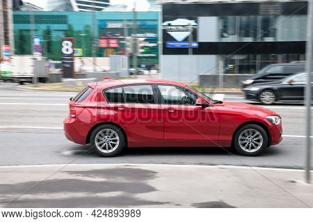 Moscow, Russia - April 2021: Side View Of Bmw 1 Series In Motion. Red Hatchback Car Moving On The St