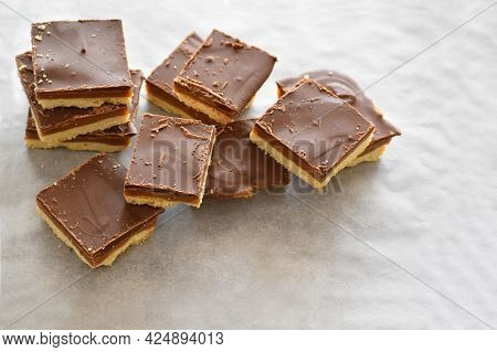 Millionaire's Shortbread With Chocolate And Caramel On Parchment Paper.