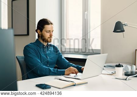 Young Focused Bearded Businessman Working On Laptop Computer Remotely, Sitting At Wooden Table Near