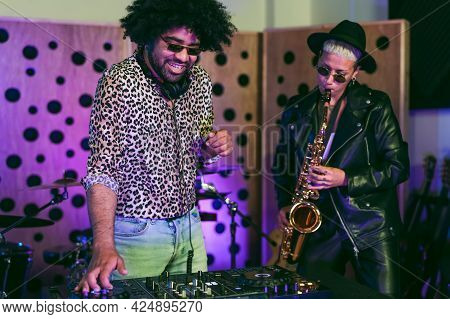 Young Happy People Playing Music With Dj Mixer And Saxophone In House Studio - Youth Musician Entert