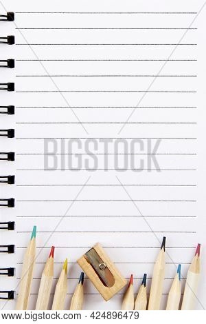 Back To School.on A Sheet Of A Notebook In A Ruler There Are Pencils With A Colored Pencil Lead And
