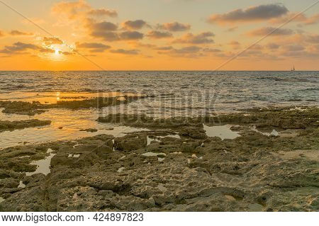Sunset View Of The Mediterranean Sea Coast, With Abrasion Platforms, And A Sailboat, In Shikmona Par
