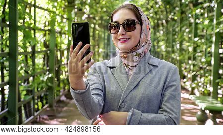 Woman In Headscarf And Sunglasses Talking On The Phone Via Video Link In The Garden Arch.