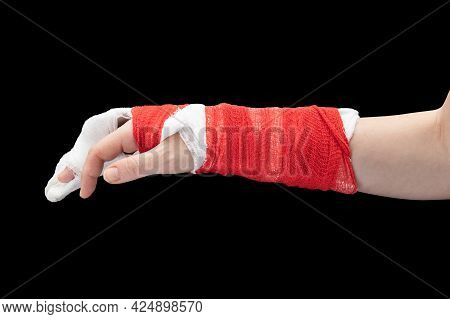 Broken Hand With White Gypsum And Red Bandage, Thumb And Index Finger Out, Isolated On Black Backgro