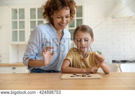 Young 35s Mother Playing Checkers With Small Daughter.