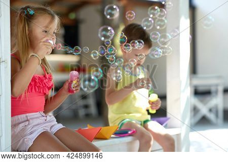 cute little girl teaching her brother how to make soap bubbles