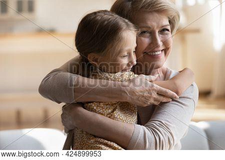 Happy Positive Elderly Granny Cuddling Small Granddaughter.