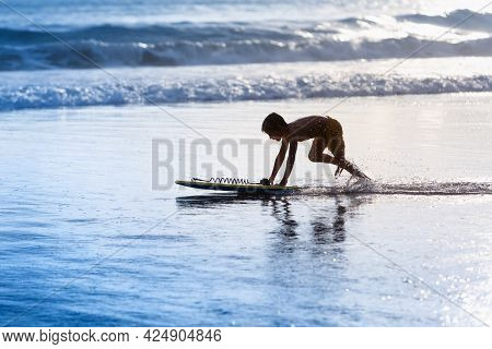 Happy Boy - Young Surfer With Bodyboard Have Fun On Beach, Run By Sea Water Pool. Active Family Life