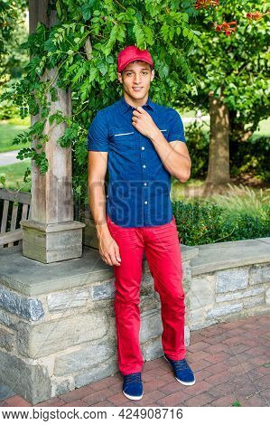 Dressing In A Red Baseball Hat, A Blue Short Sleeve Shirt,  Red Pants And Blue Shoes, A Handsome, At