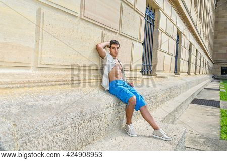 Dressing In A Iron Short Sleeve Shirt, Blue Shorts And Sneakers , A Young Attractive Guy Is Sitting