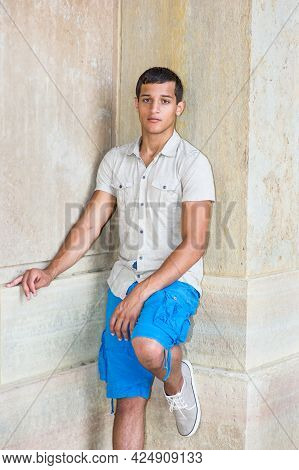 Dressing In A Iron Short Sleeve Shirt, Blue Shorts, A Young Attractive Guy Is Standing In The Corner