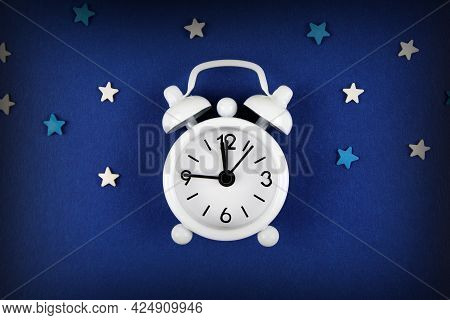 A White Alarm Clock On A Blue Background, Decorated With White And Blue Stars Around.the Concept Of