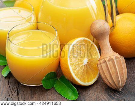 Glasses of fresh orange juice and orange fuits near them isolated on dark wooden background. Close up.