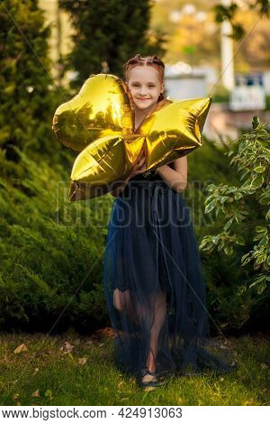 A Beautiful Little Girl With Bright Yellow Balloons In A Blue Dress Stands On A Green Background In