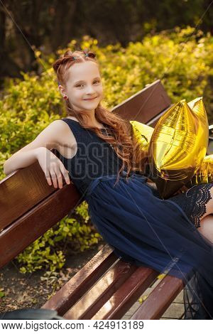 A Beautiful Little Girl With Bright Yellow Balloons In A Blue Dress Sits On A Bench In A City Park.