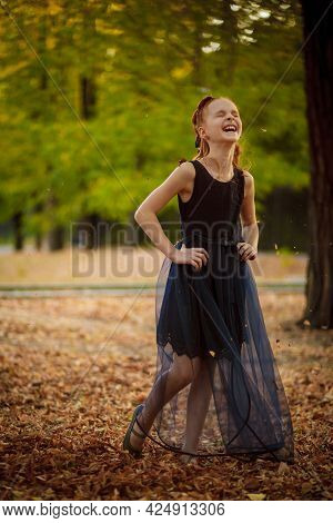 A Beautiful Little Red-haired Girl In A Blue Dress Walks In Nature In A City Park On A Warm Autumn D