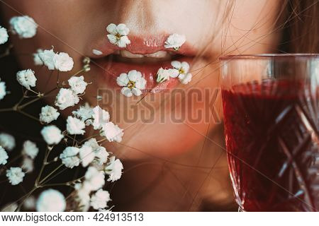 Female Lips With Little White Flowers And Graceful Glass With Red Cherry Or Strawberry Liqueur. Gent