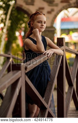 A Beautiful Little Red-haired Girl In A Blue Dress Stands On A Wooden Bridge In A City Park And Look