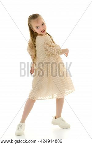 Beautiful Little Girl Is Having Fun Dancing In The Studio On A White Background. The Concept Of A Sc