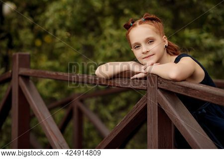 Portrait Of A Beautiful Red-haired Little Girl In A Blue Dress Who Stands On A Wooden Bridge In A Ci