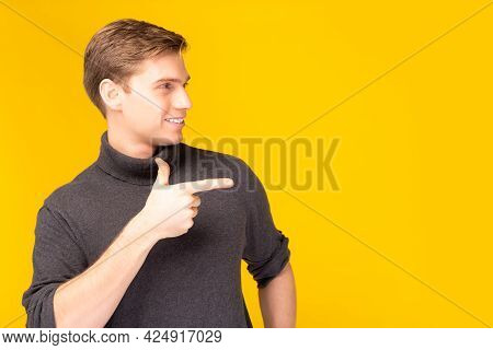 Handsome Young Man Pointing Finger To Copy Space And Looking At Space With Smile Face And Satisfied