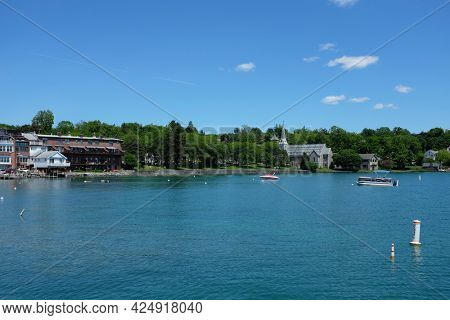 SKANEATELES, NEW YORK - 17 JUNE 2021: Thayer Park and St. James Episcopal Church on Skaneateles Lake seen from the pier.