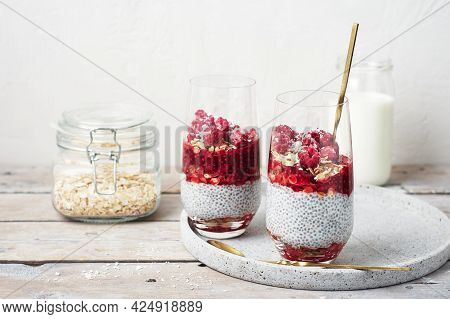 Two Glasses Of Chia Pudding With Granola And Raspberries.
