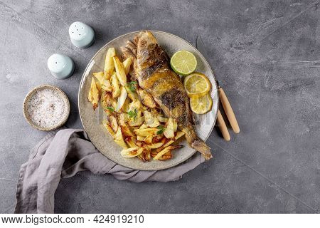 Baked Sea Bass Or Lingcod Fish With Potatoes On A Plate And Gray Background Top View, Copy Space For