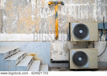 Two Old Air Conditioners Are Mounted On An Old Wall Beside The Stairs And Are Attached To An Old Yel