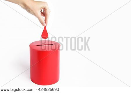 Blood Donor. Hand Puts Drop Of Blood In The Box As Donation. Concept Donate Blood Save Life. Copy Sp