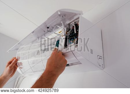 Service And Maintenance Of The Air Conditioner. The Technician Is Cleaning And Replacing The Air Con