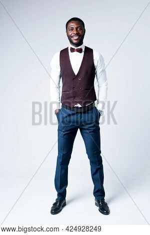 Full-length Photo. Handsome African American Businessman Standing With Hands In Pockets And Looking