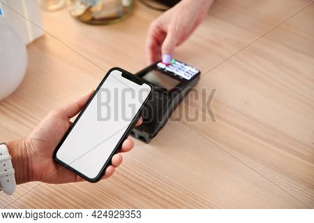 A Customer In A Cafe Makes A Contactless Payment Using An Online Application On His Phone. Close-up