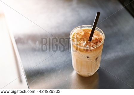High Angle View Of An Iced Coffee Latte With Straw On A Steel Counter Top In Coffee House. Refreshin
