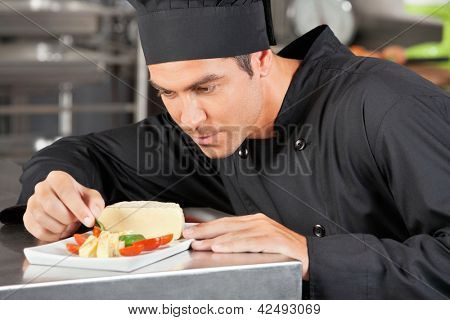 Male chef garnishing dish in commercial kitchen