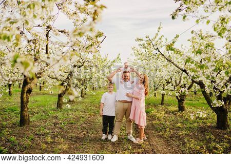 Family With Son And Daughter In Spring Flowering Garden. Cleft Lip In Infants.