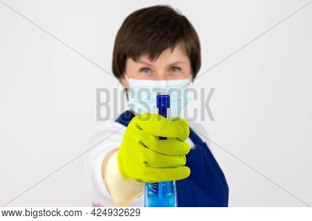 Cropped Shot Of Cleaning Lady Holding Detergent With A Spray Bottle. Woman In Uniform And Rubber Glo