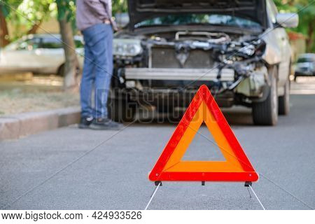 Red Triangle Warning Sign Of Car Accident On Road In Front Of Wrecked Car. Man Inspecting Wrecked Ca