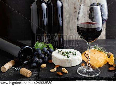 Red Wine In Classic Glass With Wine Bottles Composition. Elegant Wine Bar With Cheese Plate With Cam