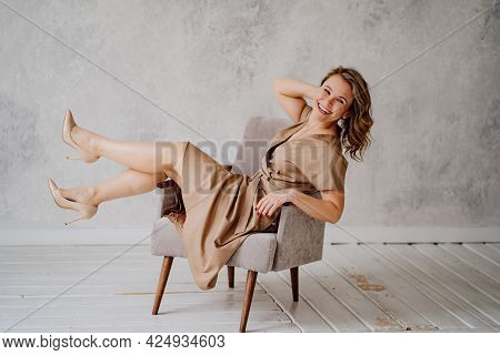 A Blonde Woman In A Beige Dress Poses On A Gray Chair In A Photo Studio.