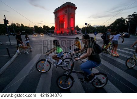 Bucharest, Romania - August 16, 2020: The Triumphal Arch Is Illuminated In Red To Mark The National