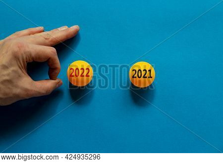 Change 2021 To 2022 Happy New Year Symbol. Male Hand Is About To Flick The Ball. Orange Table Tennis