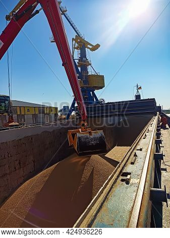 A Crane With A Manipulator Bucket Loads Wheat Onto A Dry Cargo Ship At The Berth In The Port. Loadin