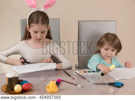 Two Sisters At The Table Draw With Paints And Cut Out Paper Crafts For The Easter Holiday. Home Crea