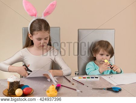 Two Sisters At The Table Draw With Paints And Markers And Cut Out Paper Crafts For The Easter Holida